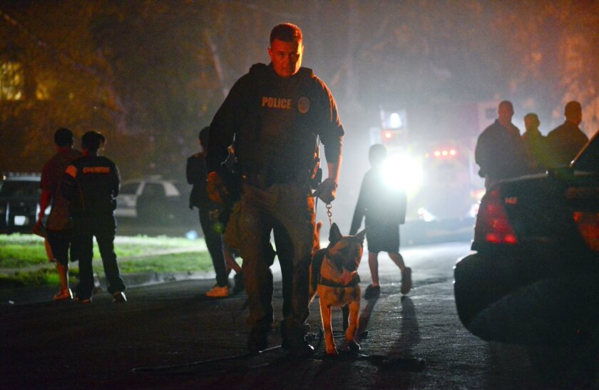 An Oceanside policeman with a police canine at the scene of a multiple shooting at Libby Lake in Oceanside on Wednesday.