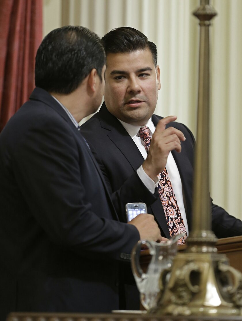 State Sen. Ricardo Lara, D-Bell Gardens, right, talks with Sen. Ben Hueso, D- San Diego, during the Senate session in Sacramento, Calif., Thursday, May 28, 2015. By a 28-11 vote the Senate approved Lara's bill, SB482, that will require California doctors to a check a statewide database before presc