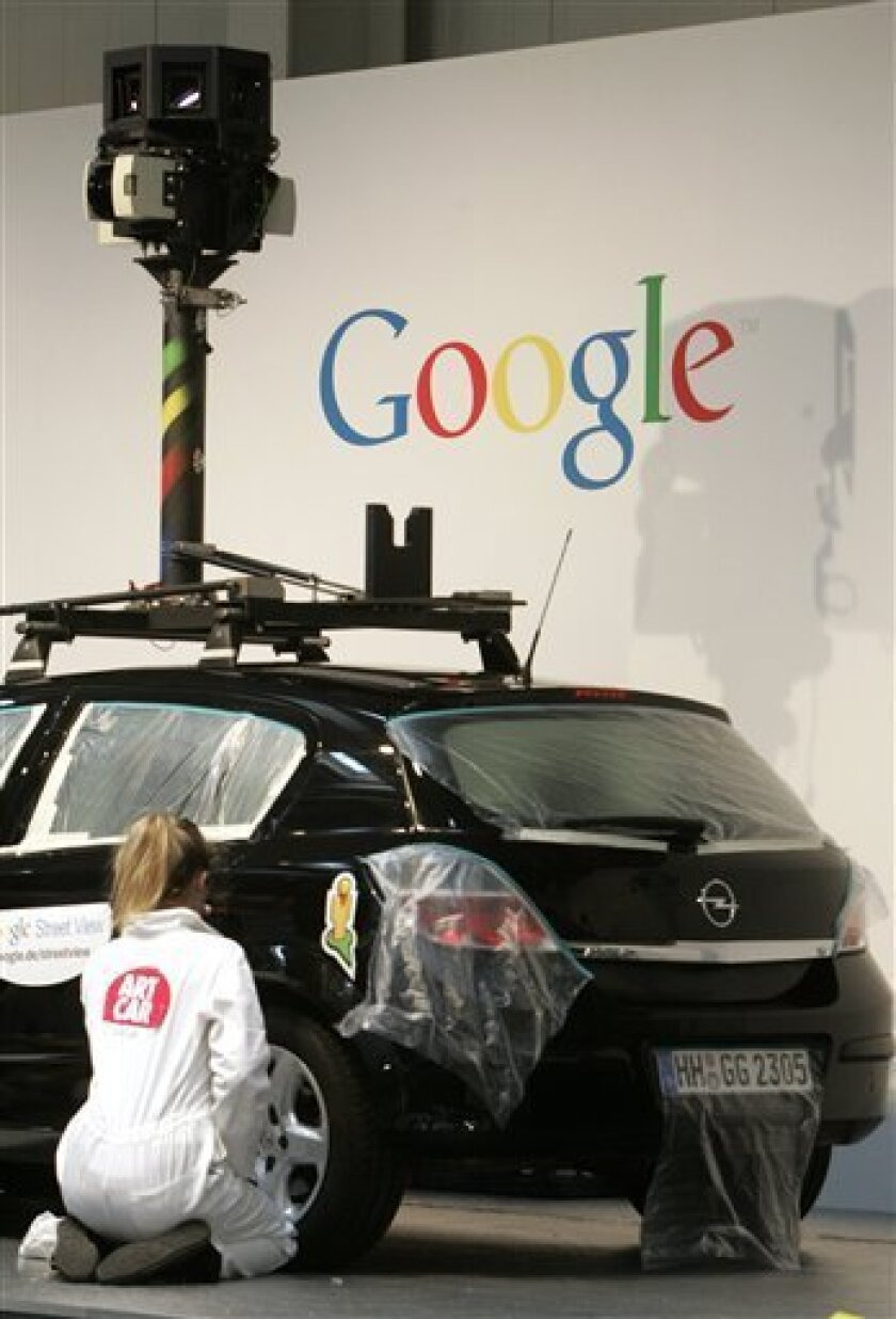 FILE - In this March 2, 2010 file photo, a woman decorates a camera car of Google at the CeBIT in Hannover, northern Germany. British authorities say Google breached data protection laws when its Street View mapping service scooped up data from private wireless networks. (AP Photo/Joerg Sarbach, File)
