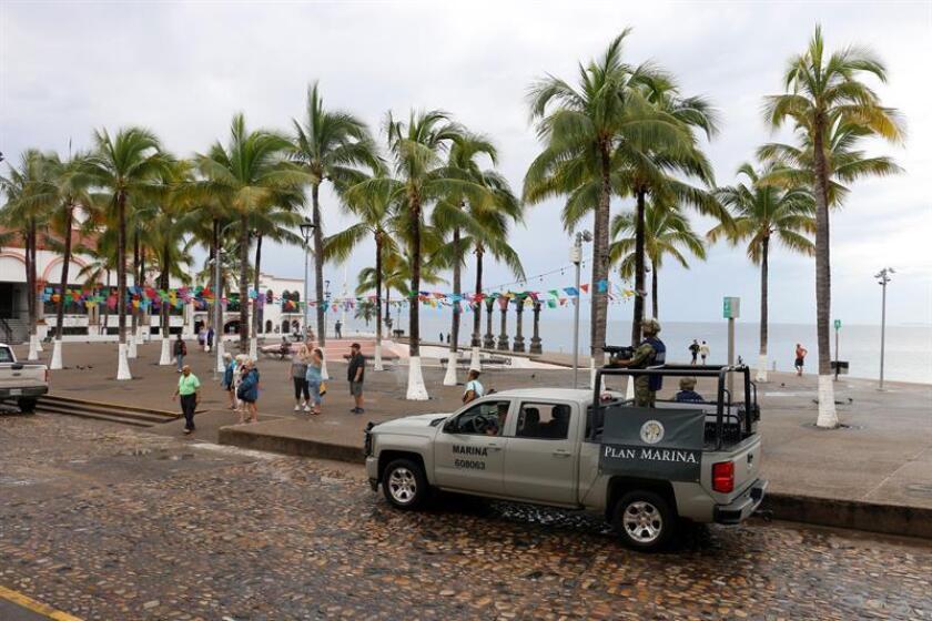Personas caminan frente a una playa en la ciudad de Puerto Vallarta (México). EFE