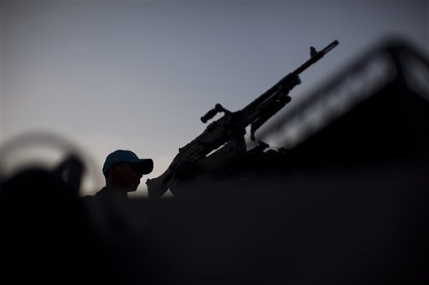A soldier stand guard at the Alemao slum complex in Rio de Janeiro, Brazil, Wednesday Sept. 7, 2011. About 100 marines deployed to help patrol the Alemao slum complex a day after soldiers were fired on by gang members in a neighboring slum that has not yet been taken over by police. More than 1,500 men and several armored vehicles from different police and military units were patrolling the area on Rio de Janeiro's north side. (AP Photo/Felipe Dana)