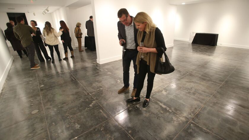 A couple explore the original flooring of the lower gallery of the Laguna Art Museum during grand op