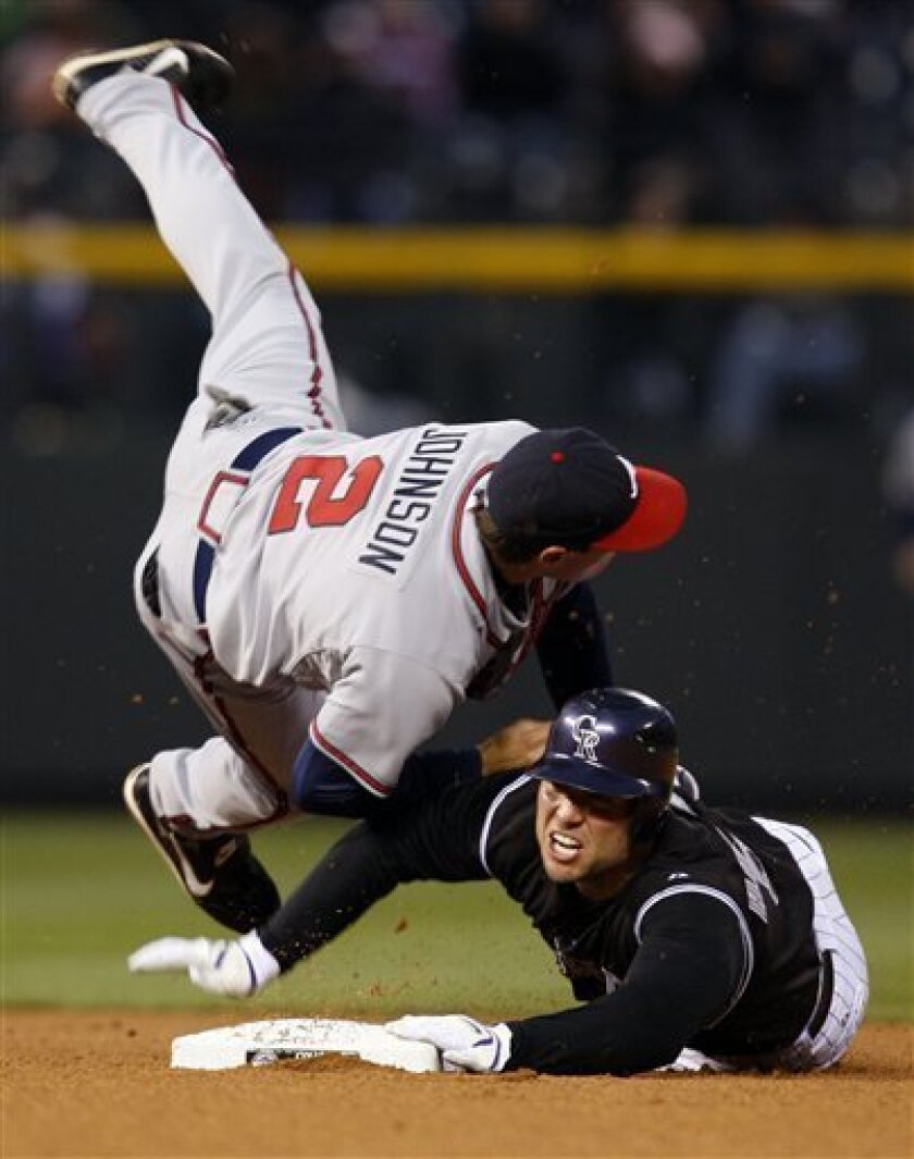 Atlanta Braves second baseman Kelly Johnson, left, is flipped in the air after forcing out Colorado Rockies' Matt Holliday, right, at seocnd base on the front end of a double play on a hit by Garrett Atkins to end the fourth inning of an MLB baseball game in Denver on Monday, April 7, 2008. (AP Photo/David Zalubowski)