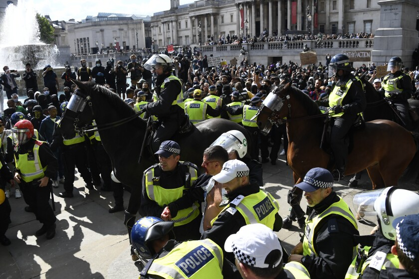 A wounded member of a far-right group is escorted by British police officers in riot gear, during scuffles as police tries to contain a protest at Trafalgar Square in central London, Saturday, June 13, 2020. British police have imposed strict restrictions on groups protesting in London Saturday in a bid to avoid violent clashes between protesters from the Black Lives Matter movement, as well as far-right groups that gathered to counter-protest. (AP Photo/Alberto Pezzali)