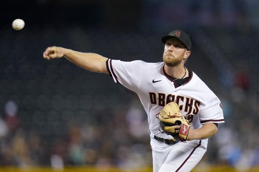 El pitcher abridor de los Diamondbacks de Arizona Merrill Kelly lanza contra los Cerveceros de Milwaukee, en el primer inning de su juego de béisbol el lunes 21 de junio de 2021 en Phoenix. (AP Foto/Ross D. Franklin)