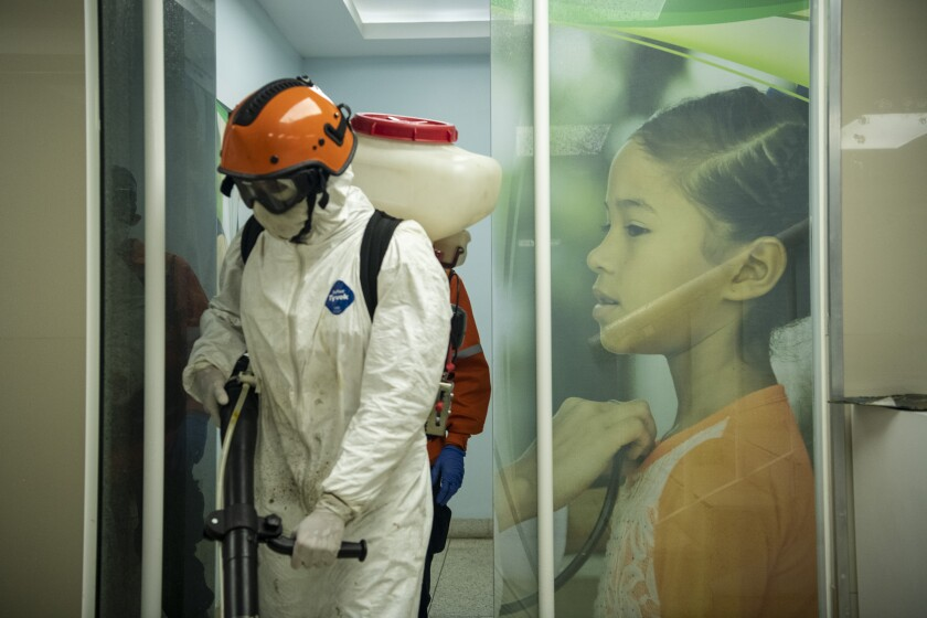 At a health center in Venezuela: a member of the disinfection squad, left, and a girl being examined.