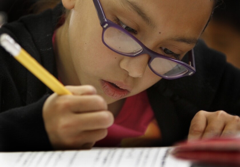 Zeimi Deleon focuses on problems during a math class at Los Angeles Elementary School in 2011.