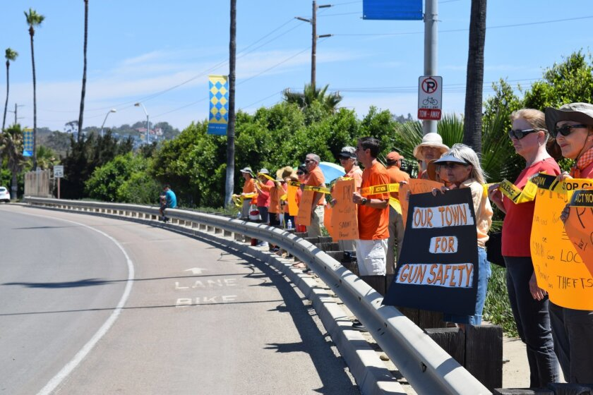 Close to two dozen people demonstrated for gun safety across the street from a July 9 gun show at the Del Mar Fairgrounds.