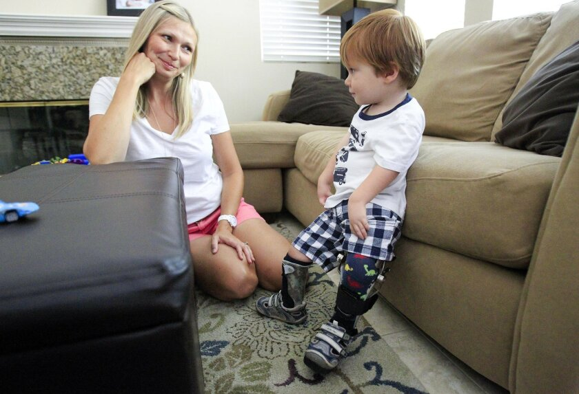 Tammy Keeline plays with her 2-year-old son Lucas, who has a rare condition known as AMC, Arthrogryposis Multiplex Congenita, which causes the joints in the body to be hooked or stiff, and the muscles to be underdeveloped.   U-T San Diego photo by Howard Lipin copyright 2014