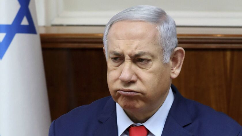 Israel's Prime Minister Benjamin Netanyahu reacts at the start of the weekly cabinet meeting at his