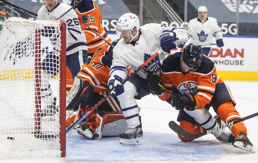 Edmonton Oilers goalie Mike Smith (41) gives up a goal to Toronto Maple Leafs' Zach Hyman (11) as Oilers' Adam Larsson (6) defends during the third period of an NHL hockey game Wednesday, March 3, 2021, in Edmonton, Alberta. (Jason Franson/The Canadian Press via AP)