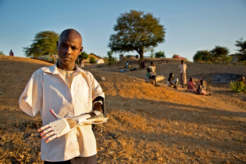 Daniel Omar, standing outside a hospital in Gidel, Sudan, wears a prosthetic arm made with a 3-D printer supplied by Not Impossible, a Venice group that helps people overcome physical limitations through technology.