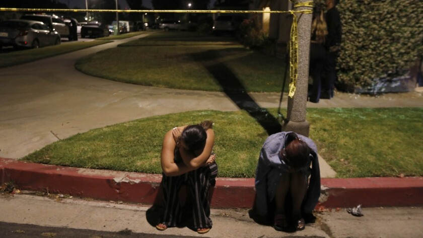 Two young women sit near crime tape on West Tiara Street in North Hollywood, where several people were shot at a house party. Two suspects have been taken into custody.