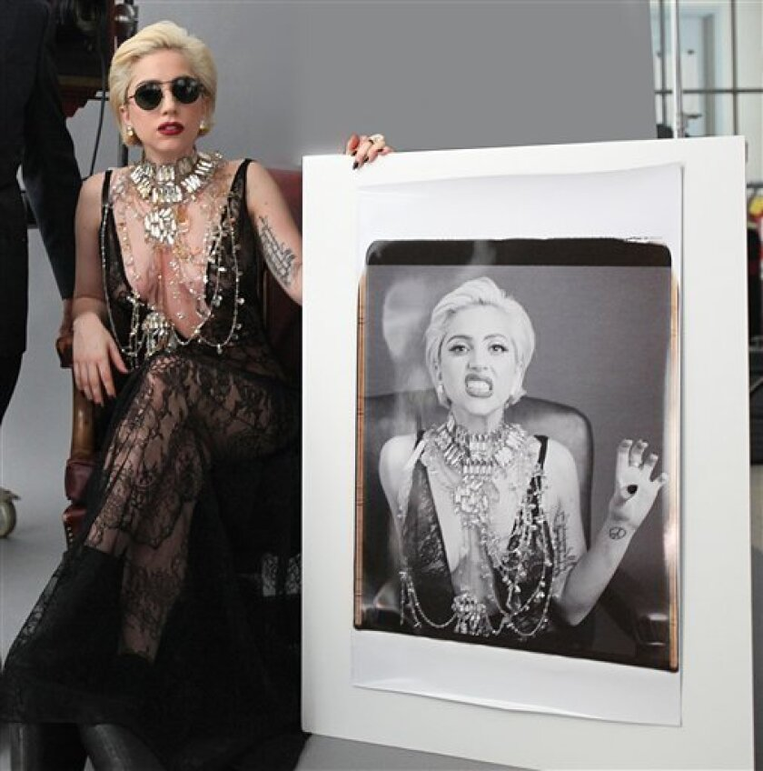 In this publicity image released by Polaroid, Lady Gaga poses with a large Polaroid picture of herself at the MIT Art Museum in Cambridge, Mass. The photo will become a part of the Museum's Polaroid archive. (AP Photo/Polaroid)