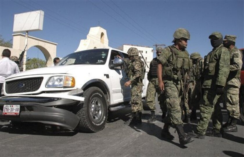 "Soldiers stand next to a vehicle during a gunfight with alleged cartel members in the northern border city of Matamoros, Mexico, Friday Nov. 5, 2010. During the operation, Mexican marines killed reputed Gulf cartel leader and one of Mexico's most-wanted drug lords, Antonio Ezequiel Cardenas Guillen, alias ""Tony Tormenta,"" or ""Tony the Storm,"" according to the Mexican navy. (AP Photo/El Bravo de Matamoros)"