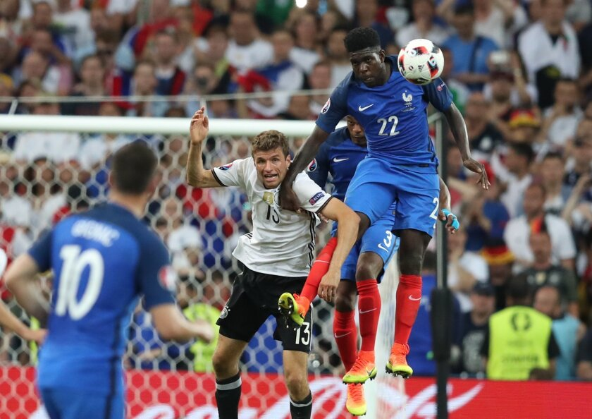 France's Samuel Umtiti, right, jumps for a header with Germany's Thomas Mueller during the Euro 2016 semifinal soccer match between Germany and France, at the Velodrome stadium in Marseille, France, Thursday, July 7, 2016. (AP Photo/Thanassis Stavrakis)