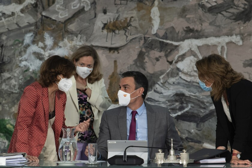 In this photo provided by the Spanish Government in Madrid, Spain's Prime Minister Pedro Sanchez, centre, speaks with three of his ministers, during a cabinet meeting at the Moncloa Palace in Madrid, Tuesday June 22, 2021. The Spanish Cabinet met on Tuesday to issue pardons for nine imprisoned Catalans who spearheaded the 2017 effort to set an independent republic in the affluent northeastern region, a move that Prime Minister Pedro Sanchez says is needed to bring reconciliation. (Borja Puig de la Bellacasa/Spanish Government via AP)