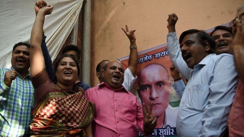 Friends of Kulbhushan Jadhav celebrate outside his childhood home in Mumbai after the alleged Indian spy was given a stay of execution.