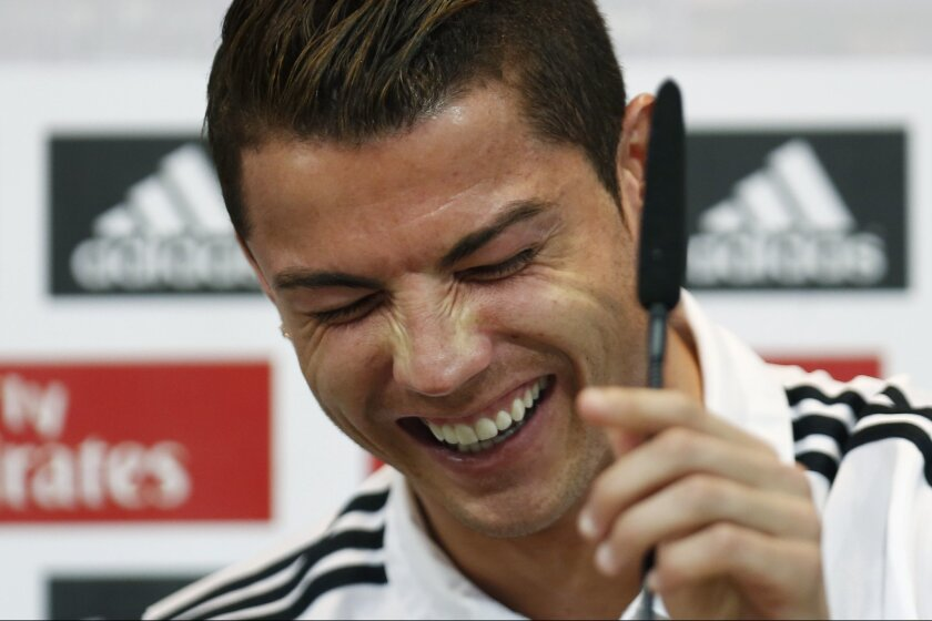 Real Madrid's Cristiano Ronaldo from Portugal laugh during a press conference on the 2014 soccer World Cup in Madrid, Spain, Sunday, Dec. 8, 2013. (AP Photo/Andres Kudacki)
