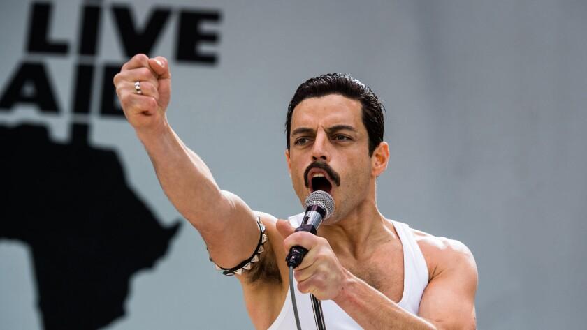 "Rami Malek as Queen's Freddie Mercury holds a microphone and raises his arm in ""Bohemian Rhapsody."""