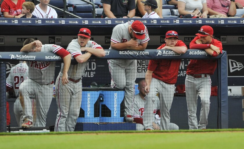 Philadelphia Phillies players lean against the dugout railing after watching the Atlanta Braves turn a double play on a Maikel Franco ground ball during the ninth inning of a baseball game, Sunday, July 31, 2016, in Atlanta. Atlanta won 2-1. (AP Photo/John Amis)