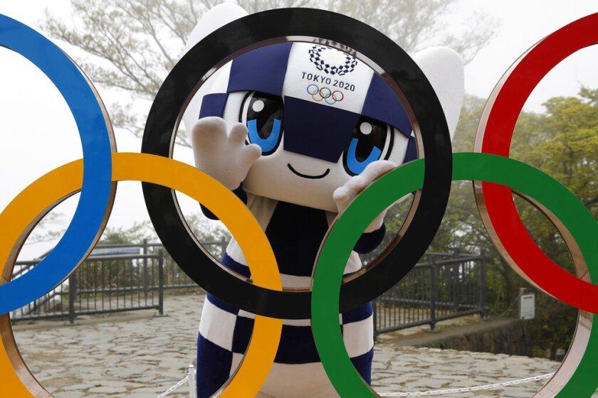 En esta imagen, tomada el 14 de abril de 2021, la mascota de Tokio 2020, Miraitowa, posa con los aros olímpicos