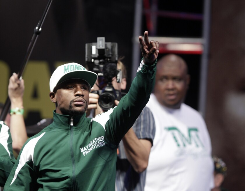 Floyd Mayweather Jr. waves to fans as he arrives on stage for his weigh-in Friday ahead of his bout with Marcos Maidana at the MGM Grand. Mayweather will defend his WBC/WBA welterweight and super-welterweight titles Saturday night.