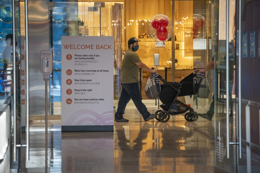 A shopper pushes a stroller past a store in South Coast Plaza in Costa Mesa on Monday.