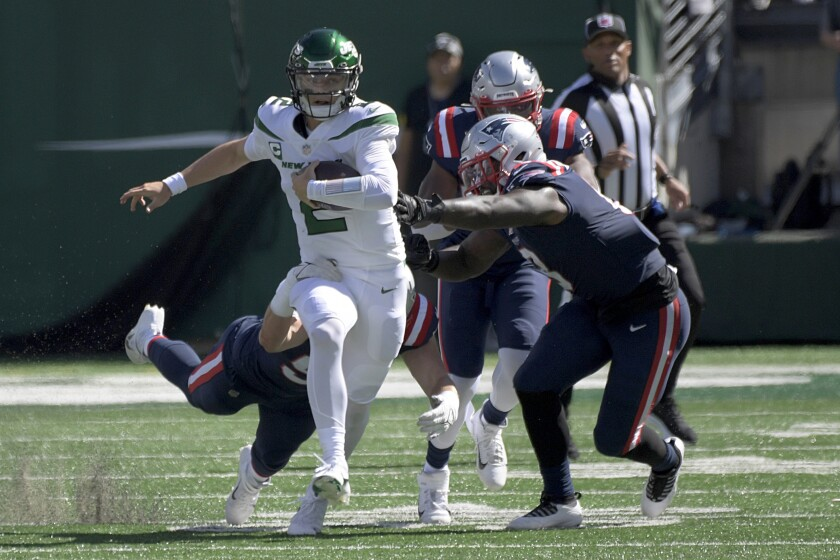 New York Jets quarterback Zach Wilson (2), left, scrambles for a first down during the second half of an NFL football game against the New England Patriots, Sunday, Sept. 19, 2021, in East Rutherford, N.J. (AP Photo/Bill Kostroun)