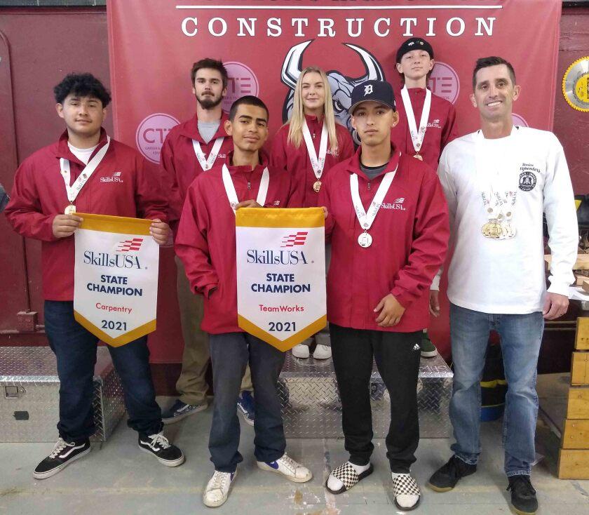 Montecito High construction teacher Nicholas Jordan, right, celebrates state SkillsUSA win with his students.