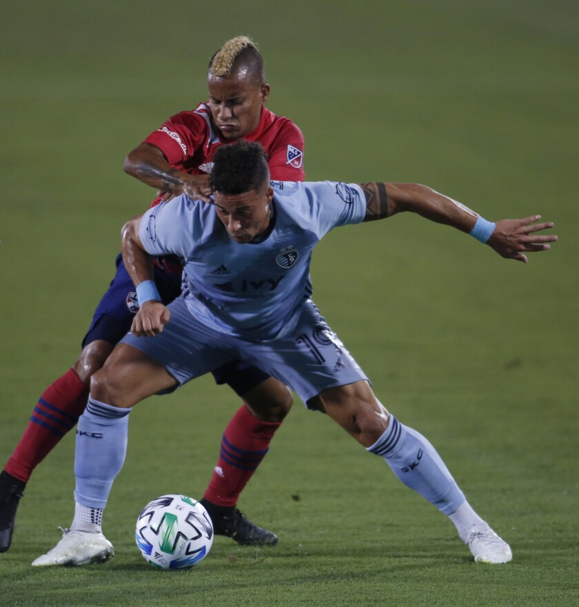 Sporting KC's Erik Hurtado, front, shields the ball from FC Dallas' Michael Barriosduring the first half of an MLS soccer game in Frisco, Texas, Wednesday, Oct. 14, 2020. (Steve Hamm/The Dallas Morning News via AP)