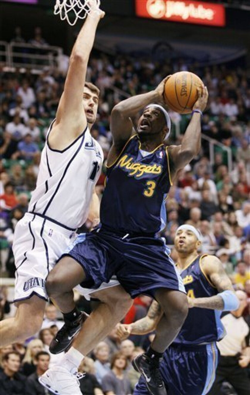 Denver Nuggets guard Ty Lawson (3) goes up for the shot against Utah Jazz center Mehmet Okur of Turkey (13) during the second period of their NBA basketball game, Saturday, Jan. 2, 2010, in Salt Lake City. (AP Photo/Colin Braley)
