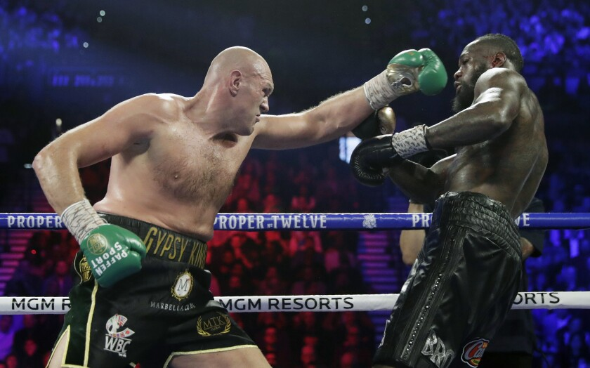 FILE - In this Feb. 22, 2020, file photo, Tyson Fury, left, of England, fights Deontay Wilder during a WBC heavyweight championship boxing match in Las Vegas. Fury is turning his attention to an all-British heavyweight unification bout with Anthony Joshua early next year after ending plans for a third fight with Deontay Wilder. Fury claimed the WBC belt from Wilder with a seventh-round stoppage in their rematch in Las Vegas in February and the British boxer's U.S. promoter, Bob Arum, was looking to stage a third fight between them in front of 15,000 spectators at the home of NFL team Las Vegas Raiders on Dec. 19. (AP Photo/Isaac Brekken, File)