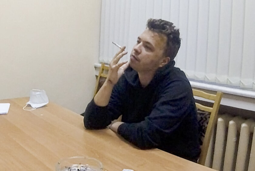 In this handout photo released by ONT channel on Wednesday, June 2, 2021, dissident journalist Raman Pratasevich smokes a cigarette while speaking in a video from a detention center in Minsk, Belarus. The footage of Raman Pratasevich was part of an hour-long TV program aired late Wednesday by the state-controlled ONT channel. In the film, the 26-year-old Pratasevich is also shown saying that protests against Belarus' authoritarian President Alexander Lukashenko are now pointless amid a tough crackdown and suggesting that the opposition wait for a more opportune moment. (ONT channel VIA AP)