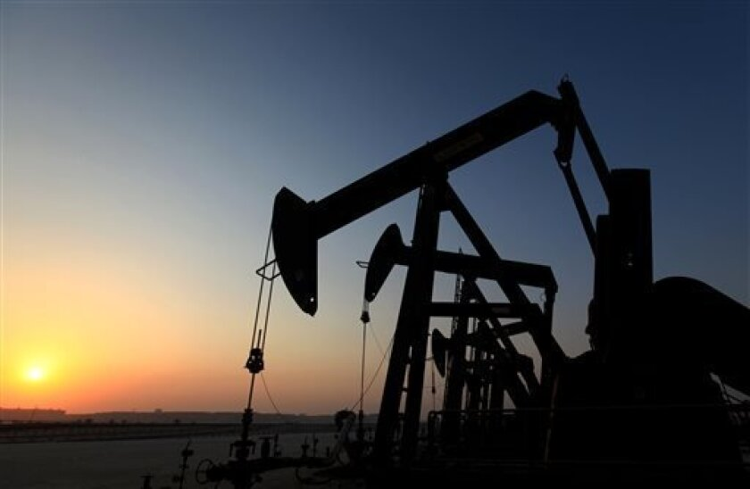 A row of oil pumps work at sunset Wednesday, Sept. 11, 2013, in the desert oil fields of Sakhir, Bahrain. The price of oil rose Wednesday as the market waited for the next developments regarding Syria. (AP Photo/Hasan Jamali)