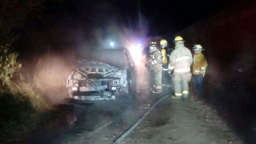 Un grupo de bomberos apagan el fuego de un vehículo en el que se encontraban siete personas hoy, viernes 1 de diciembre de 2017, en el municipio de Uruapan, en el estado de Michoacán (México). EFE/STR