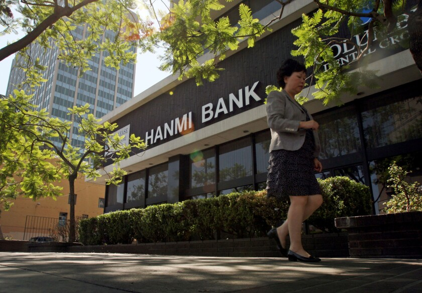 A passerby walks near the Hanmi bank building in L.A.'s Koreatown. The bank has withdrawn its proposed merger with rival Korean American lender BBCN.