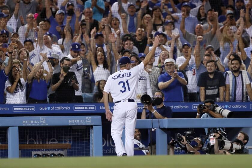 El pitcher abridor de los Dodgers de Los Ángeles Max Scherzer recibe una ovación al marcharse en el séptimo inning de su juego de béisbol contra los Astros de Houston en Los Ángeles, el miércoles 4 de agosto de 2021. (AP Foto/Alex Gallardo)