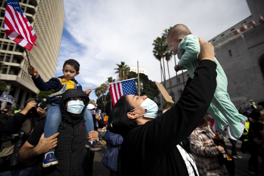 Abeer Mahmoud, 35, holds up her daughter Asset Taha, age 3 months, right, during a celebration outside Los Angeles City Hall.