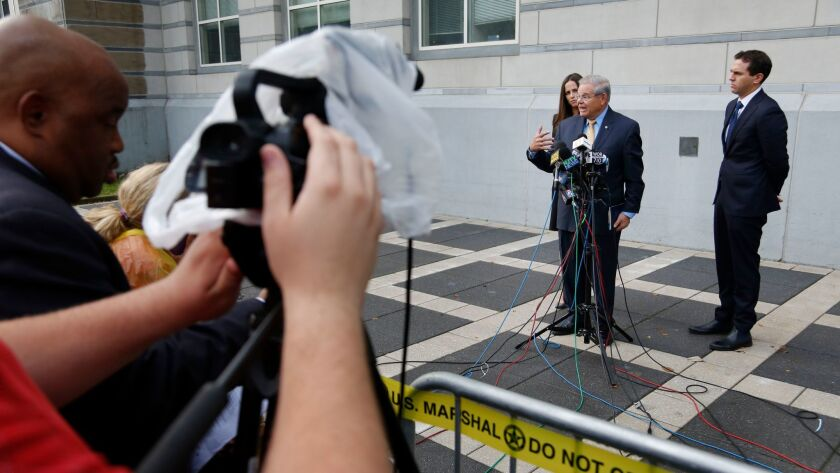 Sen. Bob Menendez, second from right, talks to reporters while his children, Alicia Menendez and Robert Menendez Jr., look on outside the courthouse in Newark, N.J., on Sept. 6.