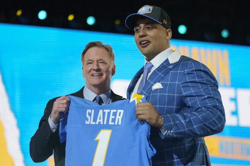 Northwestern tackle Rashawn Slater, right, holds a team jersey with NFL Commissioner Roger Goodell after the San Diego Chargers selected him with the 13th pick in the NFL football draft Thursday April 29, 2021, in Cleveland. (AP Photo/Tony Dejak)