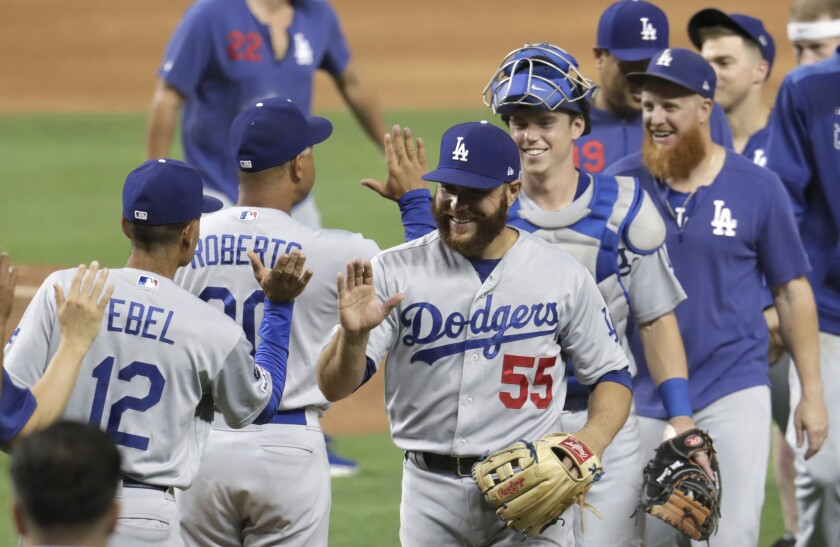 Member of the Dodgers high-five each other after beating the Miami Marlins on Tuesday in Miami. The Dodgers won 15-1.