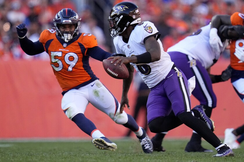 Baltimore Ravens quarterback Lamar Jackson (8) looks to throw under pressure from Denver Broncos linebacker Malik Reed (59) during the second half of an NFL football game, Sunday, Oct. 3, 2021, in Denver. (AP Photo/Jack Dempsey)