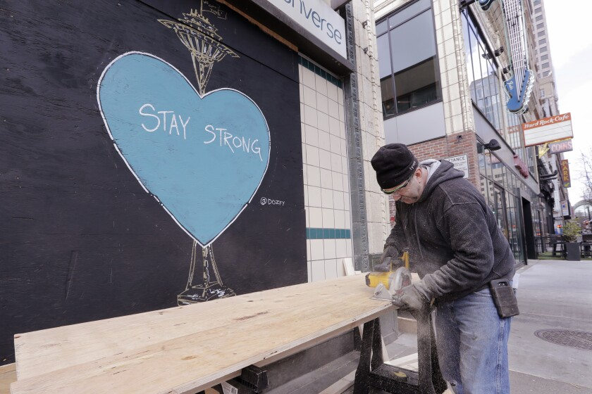 A carpenter cuts plywood to cover a closed store where artwork in support of people affected by the coronavirus already covers an adjacent panel in downtown Seattle on  Thursday.