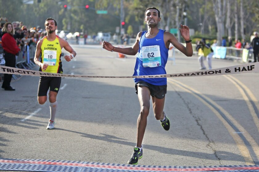 First place men's finisher in the Tri-City Medical Center Carlsbad Half Marathon Yonas Mebrahtu breaks the finish tape ahead of second place finisher Soufiane Bouchikhi Sunday. photo by Bill Wechter