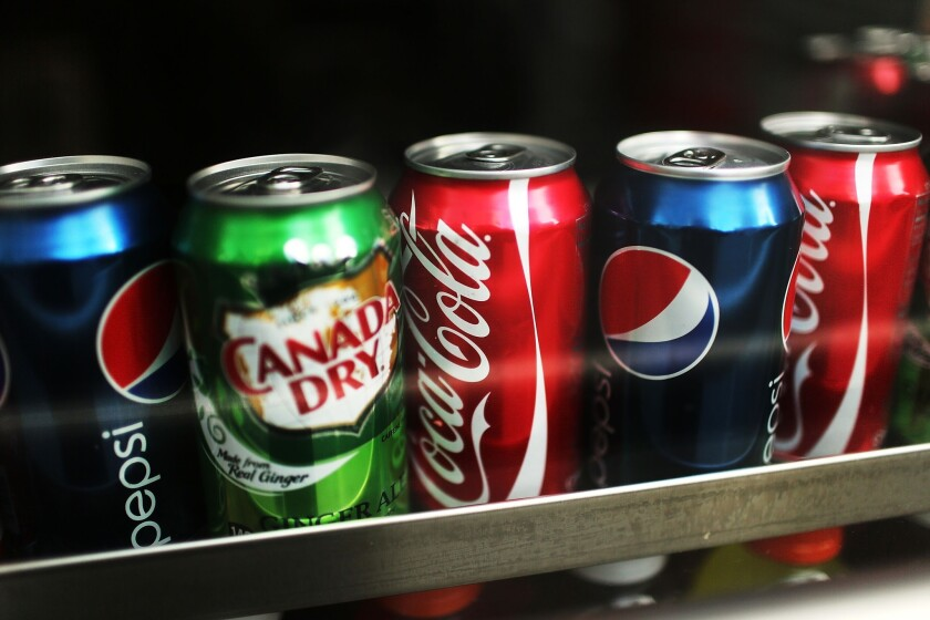 Cans of soda are displayed on a shelf in New York City. A new taste modifier called S617 could reduce the amount of sugar in future soda products.