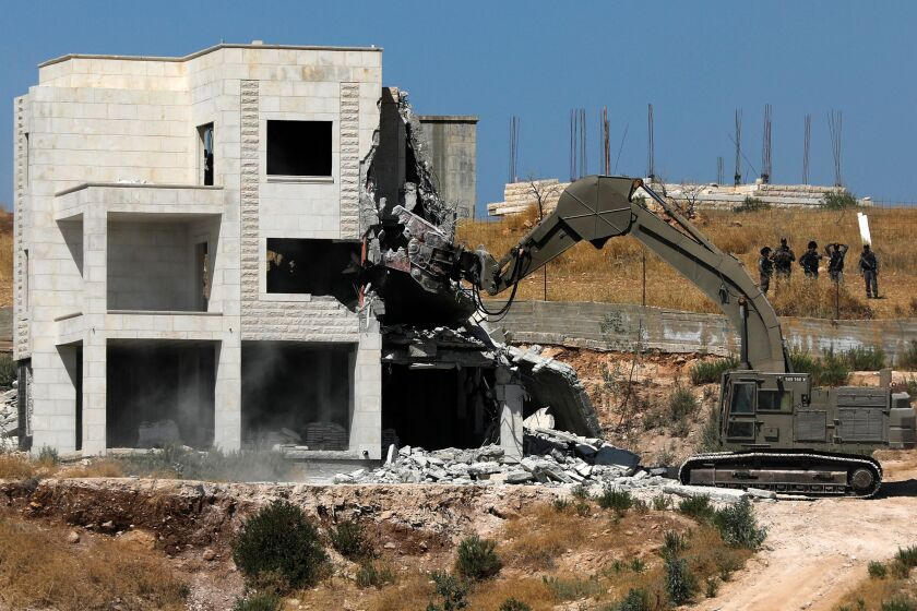 Israeli security forces tear down one of the Palestinian buildings still under construction in the West Bank village of Dar Salah on Monday.