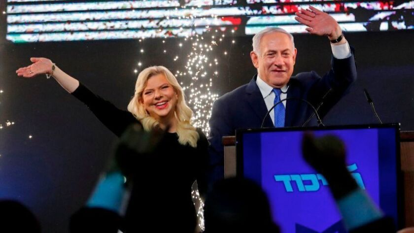 Israeli Prime Minister Benjamin Netanyahu, accompanied by his wife Sara, greets supporters at the Likud Party headquarters in Tel Aviv on election night early on April 10.