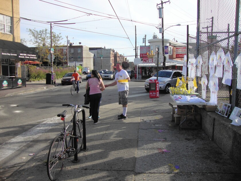 """Michael """"Puge"""" Puggi, 40, sells Vatican flags on a busy corner in South Philadelphia."""