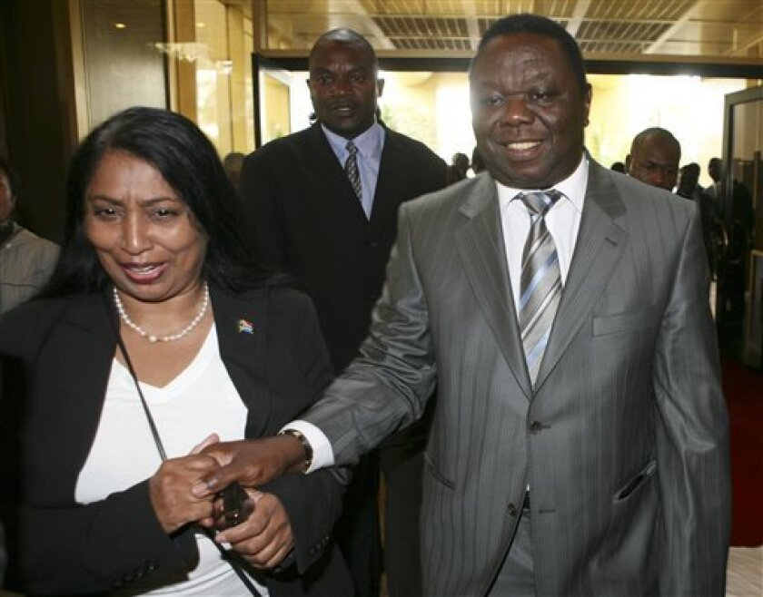 Zimbabwe's opposition leader Morgan Tsvangirai, right, is escorted by South African Home Affairs official Priscilla Naildoo, upon his arrival at a local hotel in Harare, Monday, Jan. 19, 2009. Zimbabwe's President Robert Mugabe and Tsvangirai are holding new power-sharing talks, a day after both ru